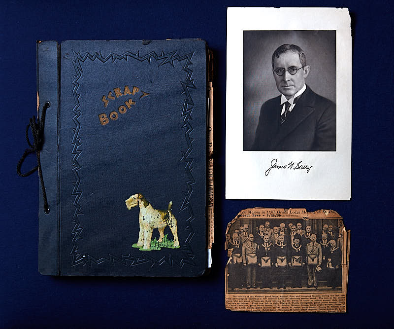 Newspaper clipping, blue scrapbook with dog on front, and signed photo on blue background.