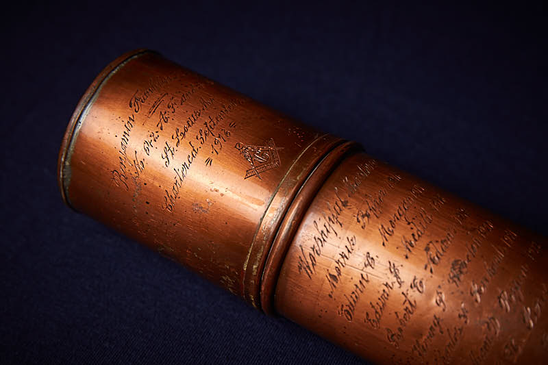 Bronze cylinder case with engraved names on it.