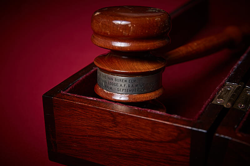 Close up of a wooden gavel with a silver band placed in a wooden box.