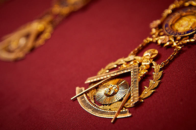 Close up shot of a gold masonic jewel.